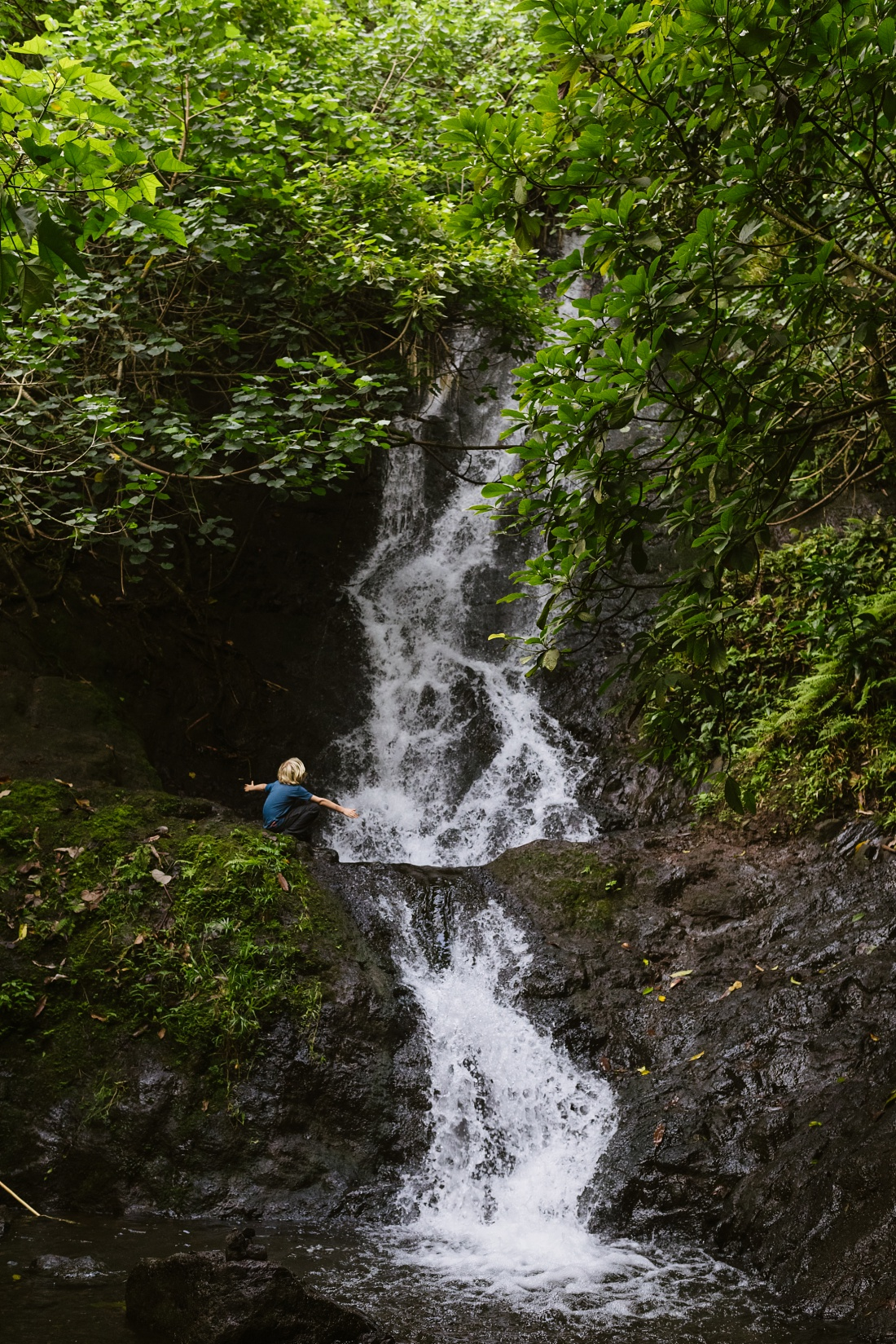 boy enjoying a waterfall in hawaii