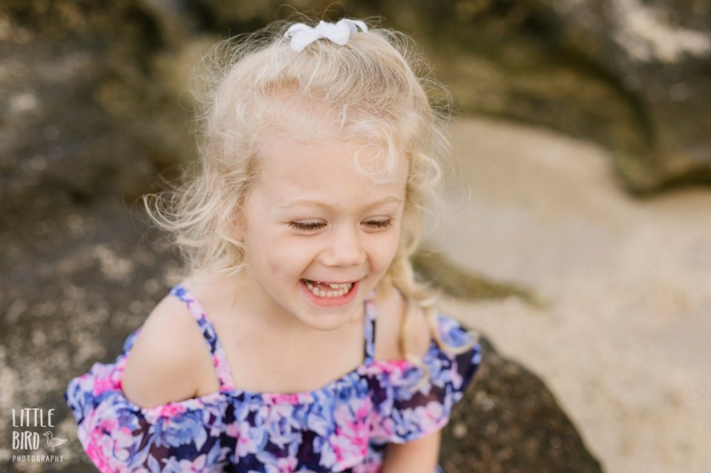 little girl laughs during a family portrait session at a beach in hawaii