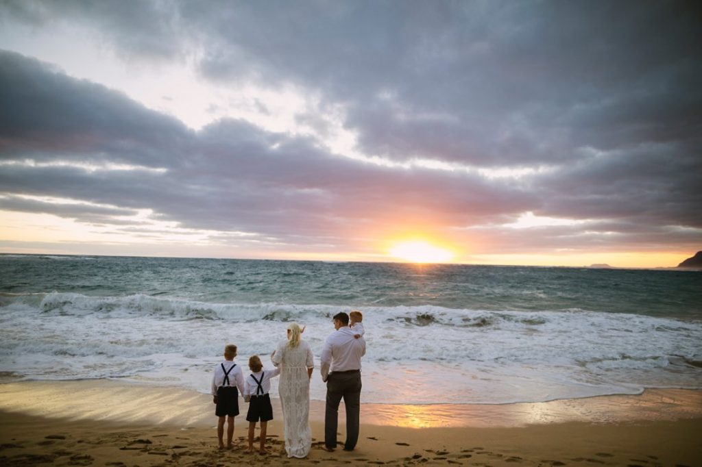 family taking in sunrise during a hawaii vow renewal cermony